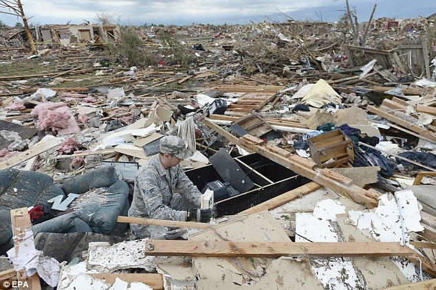 US Air Force Airman First Class Justin Acord sifts through the rubble of his father-in-law's home in Moore, Oklahoma, USA, 21 May 2013