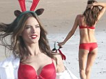 Alessandra Ambrosio gets in the festive spirit with reindeer antlers and red lingerie as she frolics on the beach for Victoria's Secret