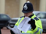 If your name's not down, you're not coming in: Two officers check to see who has made it for the Christmas lunch