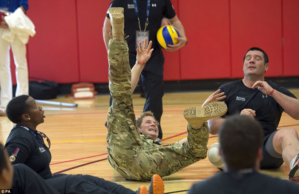 Tumble: Prince Harry meets British soldiers competing in the warrior games and plays sitting volleyball with them in Colorado Springs
