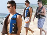 Simon Cowell is pictured on the beach and enjoying a jet ski ride while on holiday in Barbados