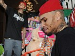 Looks like the anger management's working! Smiling Chris Brown greets fans at charity event during brief break from rehab