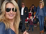 Modern family! Penny Lancaster, 42, carries her own luggage while husband Rod Stewart, 68, takes care of son Aiden, aged two, as they touch down in Miami