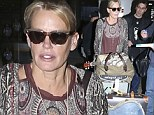 No star trip here! Daryl Hannah goes Bohemian in burgundy print blouse while pushing her own cartload of luggage at LAX