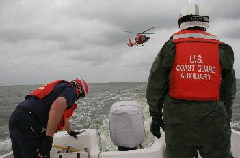 photo of crewmembers preparing for basket lowering at stern of boat. USCG helo visible in background.