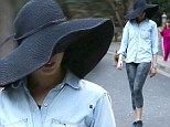 Who's that girl? Anne Hathaway plays hide and seek under a giant hat as she heads out for her daily walking workout