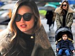 Designer doubles: Miranda Kerr and son Flynn don matching fur-trimmed coats during a rainy city stroll