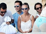 Best spot of all! Chloe Green sits on Marc Anthony's lap in white fringed shorts as they cosy up during family boat trip