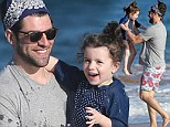 He loves his New Girl! Max Greenfield larks about with daughter Lily in the surf in Hawaii