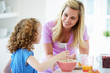 Mother And Daughter Having Breakfast In Kitchen Together