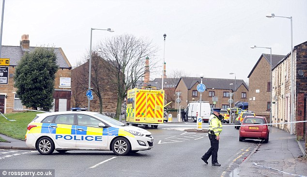 Police have thrown a cordon around a siege involving a man holding a woman hostage with a knife in Burnley