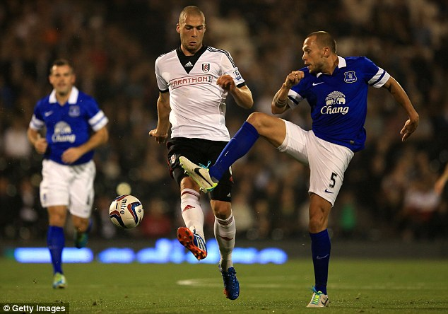 On the move: John Heitinga (right) is leaving Everton to join West Ham's battle against relegation