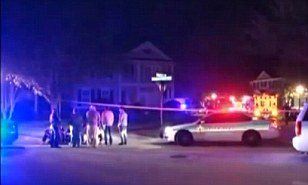 Somber scene: Neighbors gathered as police roped off the area and began their investigation