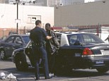 Cleaning the streets: An officer with the LAPD arrests a man who has been found on the corner of a Skid Row avenue - as they begin a process which started in 2006