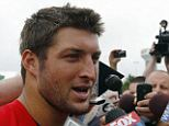 Behind the mike: Former NFL quarterback Tim Tebow talks to reporters during his short spell at the New England Patriots. He is now taking a job as a TV analyst with ESPN