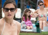 Katie Holmes slips her toned figure into bikini top and cut-offs as she sunbathes with daughter Suri in Miami