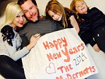 'Happy New Year, love The McDermotts!' Tori Spelling cuddles up to husband Dean for family photograph as they put reports of his infidelity firmly behind them