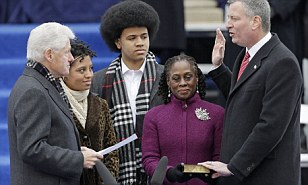 Former President Clinton delivers the oath to Bill de Blasio as his family look on