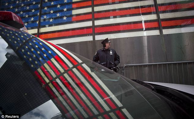 Iconic: The U.S. flag is reflected in the window of a police car as a police man stands guard in Times Square ahead of New Year's Eve celebrations in New York