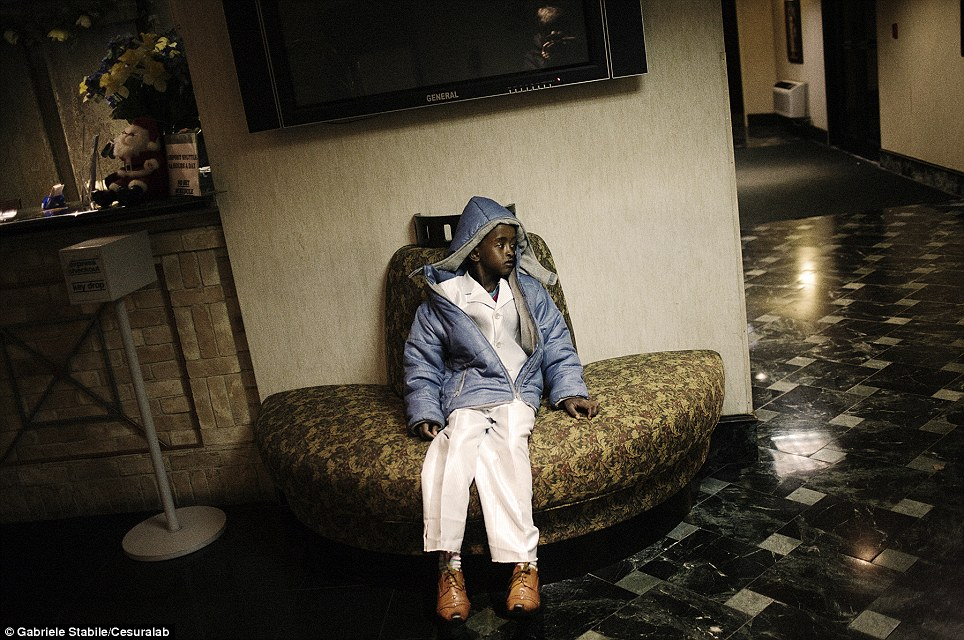 A Somali boy waits in the lobby of a hotel in Newark, New Jersey, as staff look for a room for him and his sister