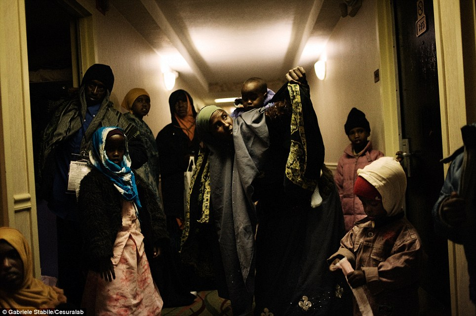 Afraid of being separated again, a family from Somalia spends the night in the hallway of a Newark hotel