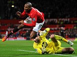 Felled: Ashley Young goes down in the area under the challenge of the French Tottenham goalkeeper