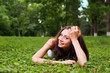 Smiling young woman lying on green grass