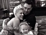 'Happy New Year!' Pink cuddles by the fire with husband Carey Hart and daughter Willow during snowy holiday in the mountains