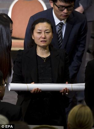 Lu Lingzi's aunt, Ting Lu, accepts 'papers' on behalf of the family. Papers are a traditional gift of remembrance: sheets of paper signed by countless students with messages of love and bereavement