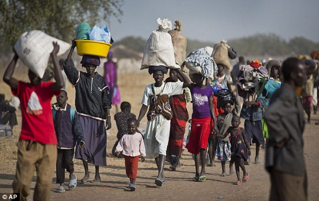 Desperation: Displaced people walk to find an unoccupied patch of ground where they can rest after arriving by river barge from Bor on Thursday. They are fleeing from fighting between government and rebel forces in Awerial, South Sudan