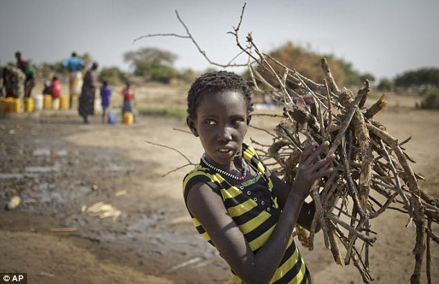 Fuel and water: In this photo taken on Thursday, January 2, a displaced girl returns from gathering firewood while others, left, extract water from a well