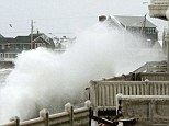 Waves crash into houses on Lighthouse Road during a winter snow storm in Scituate, Massachusetts as an alert was raised over coastal flooding