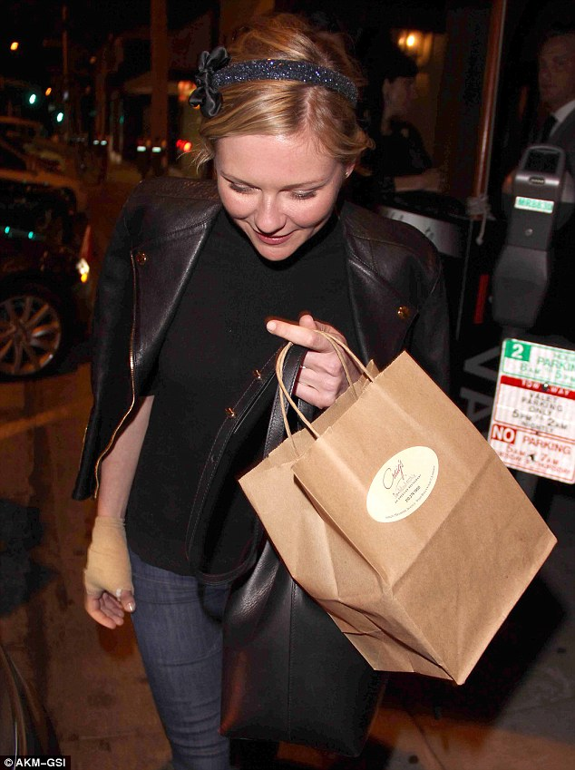 The girl's got baggage: The 31-year-old actress clutches her handbag and a brown carry out bag from Craig's in her left hand, while her injured right hand remains free