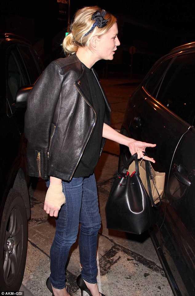 A spot of bother: One-handed Kirsten attempts to pull open her car door while still carrying her two bags