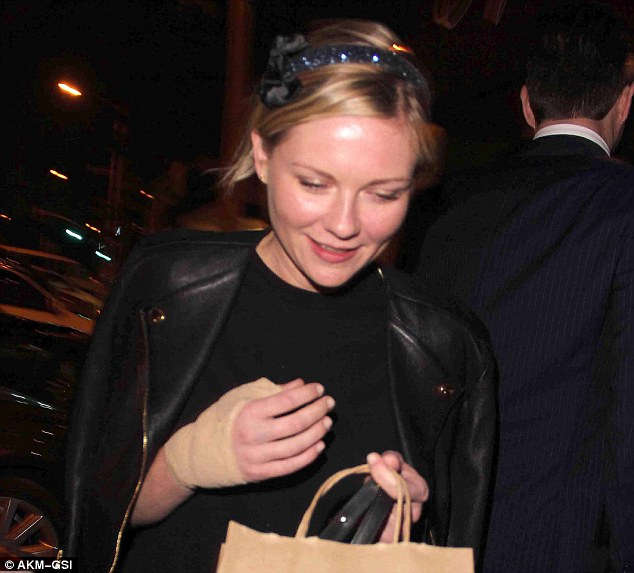 That looks sore: Kirsten Dunst reveals her bandaged hand during a night out with boyfriend Garrett Hedlund at popular restaurant Craig's in West Hollywood on Thursday evening