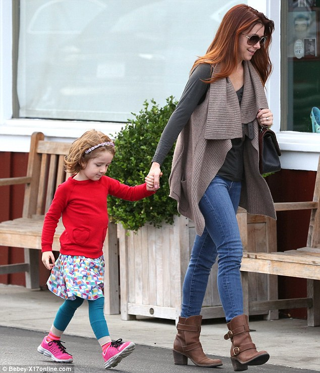 Dressing for warmth: The actress wrapped up in a long-sleeved T-shirt, skinny jeans and a woolly vest while Satyana looked cute in a red sweatshirt, multi-coloured skirt and turquoise leggings