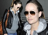 Hiding in plain sight: Pregnant Olivia Wilde continues to conceal her bump as she returns to home after New York jaunt