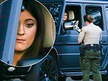 Kylie looked glum as an officer wrote out a ticket after stopping her vehicle in Malibu, California