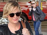 Bed-headed Amy Poehler flashes signature smirk upon landing at LAX ahead of the Golden Globes