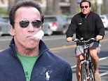 No girly man! Arnold Schwarzenegger rides a bike and is spotted smoking a cigar in a very masculine day