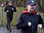 Fighting fit and proud: Ricky Gervais pounds the streets in muddy trainers on New Year jog
