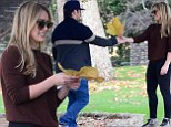 Hilary Duff smiles after being presented with a leaf by husband Mike Comrie during romantic park stroll
