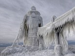 Entombed by the weather: This lighthouse in Michigan resembles a giant icicle after crashing waves were frozen around it by a severe winter storm