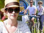 Not so breezy riders! Anne Hathaway and husband Adam Shulman look glum as they cycle in Hawaii together