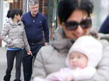 Beating the winter blues: Alec Baldwin, right, and his wife Hilaria, middle, braved the cold to take their daughter Carmen on a walk in the Hamptons, New York on Saturday