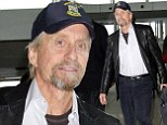 Where's Catherine? Michael Douglas sports scruffy beard as he flies to Los Angeles solo after recently reuniting with his wife