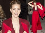 Amy Adams hustles with her coat as she covers plunging red gown after picking up Golden Globe for Best Actress