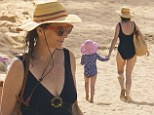 Award-winning physique: Brothers & Sisters star Rachel Griffiths shows off slender figure playing with her children on the beach