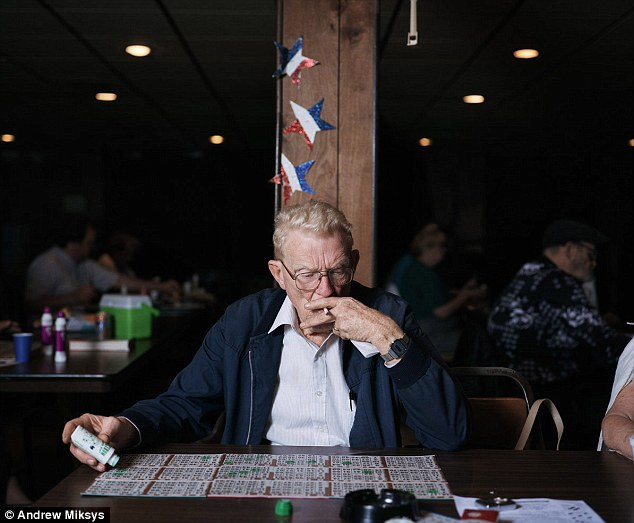 Eyes down: A bingo player smokes a cigarette as his hand hovers over a spread of cards