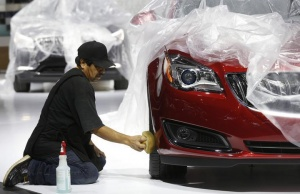 Auto show worker Jorge Martinez details a General Motors vehicle under wraps, as they prepare the displays for the media preview of the North American International Auto Show at Cobo Center in Detroit, Michigan January 11, 2014. REUTERS/Rebecca Cook